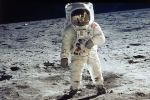 Apollo 11 astronaut Buzz Aldrin standing on moon, with astronaut Neil Armstrong & lunar module reflected in helmet visor